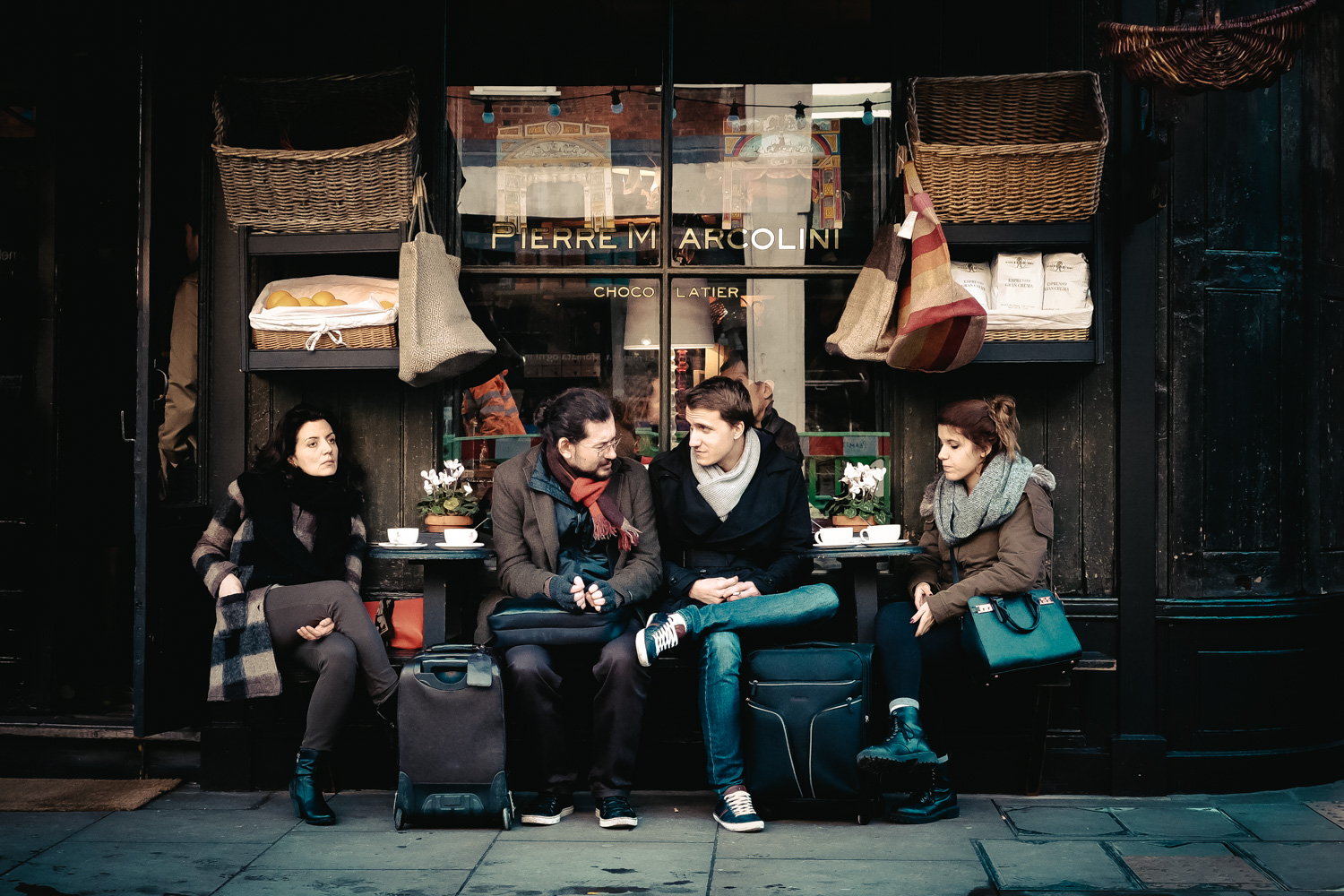 Four people sit outside an upmarket cafe with coffee.
