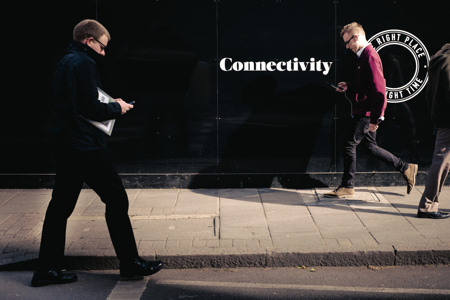 Two men walk in the city paying attention to their mobile phones. On the hording behind them the word 'Connectivity'.