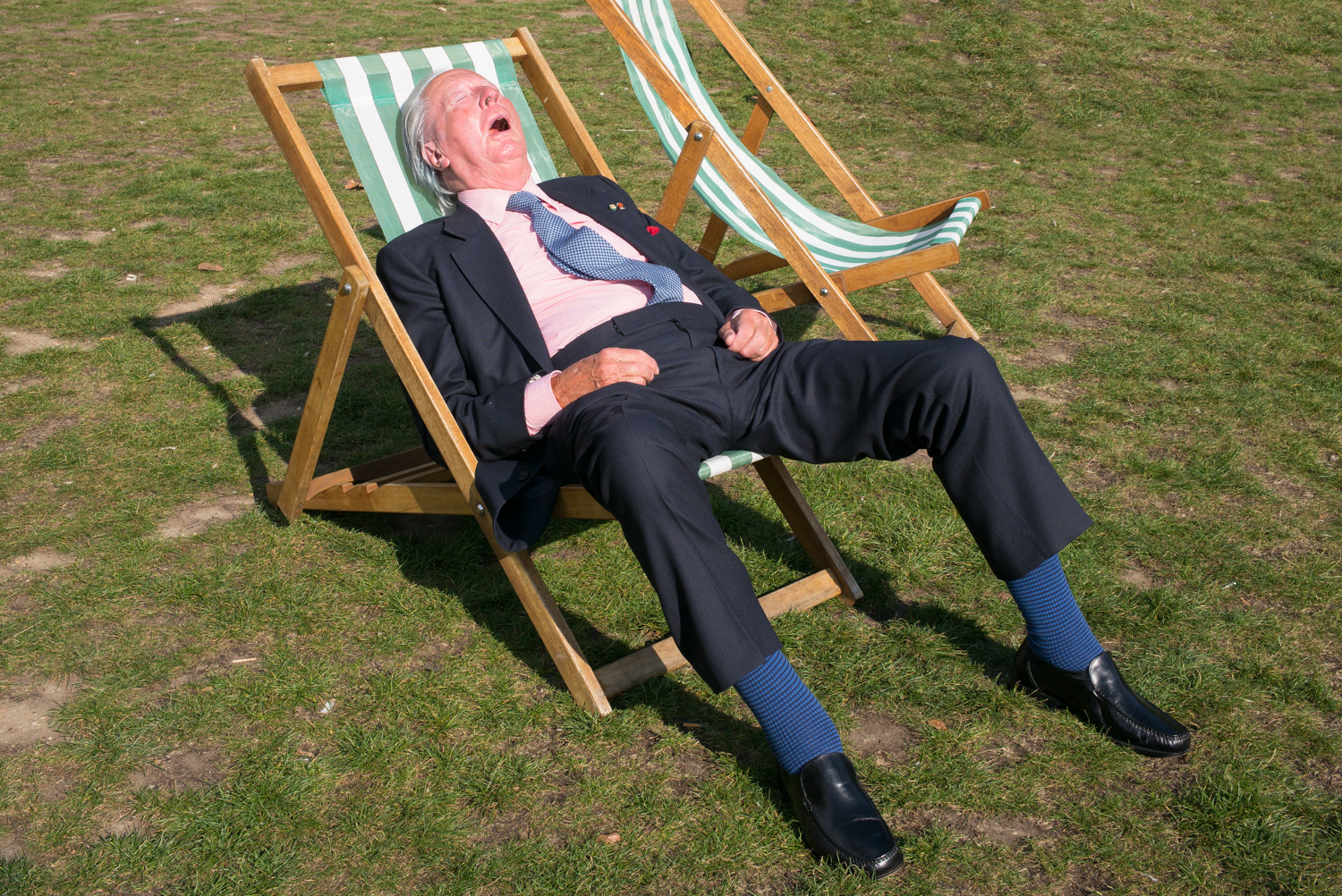 Elderly man sleeping in deckchair in the sunshine