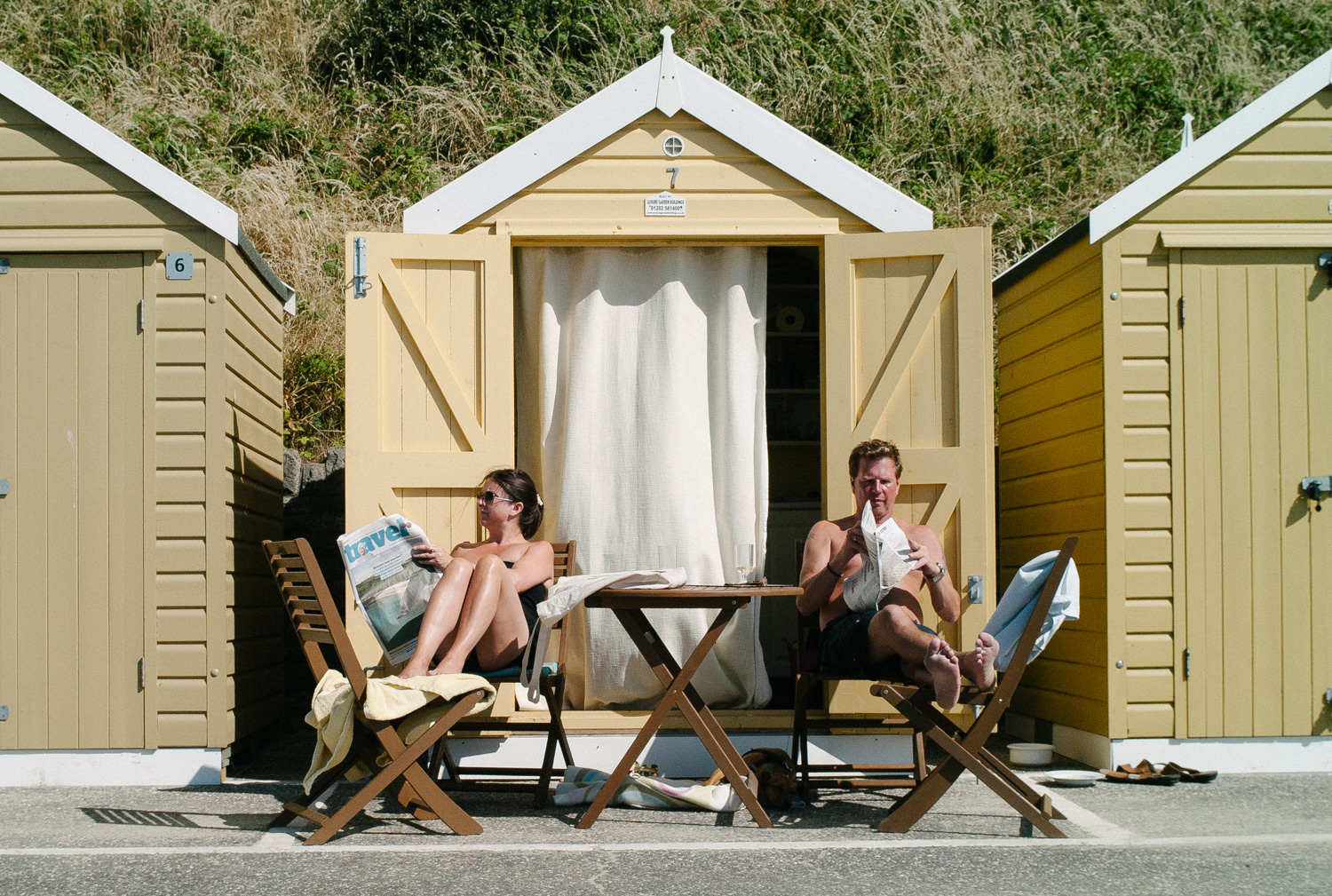 Two people reading newspapers outside a beach hut, by Gary Perlmutter