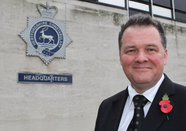 David Lloyd, Police and Crime Commissioner for Hertfordshire, standing in front of a Hertfordshire Police sign